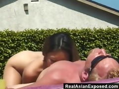 oriental widening her legs by the pool